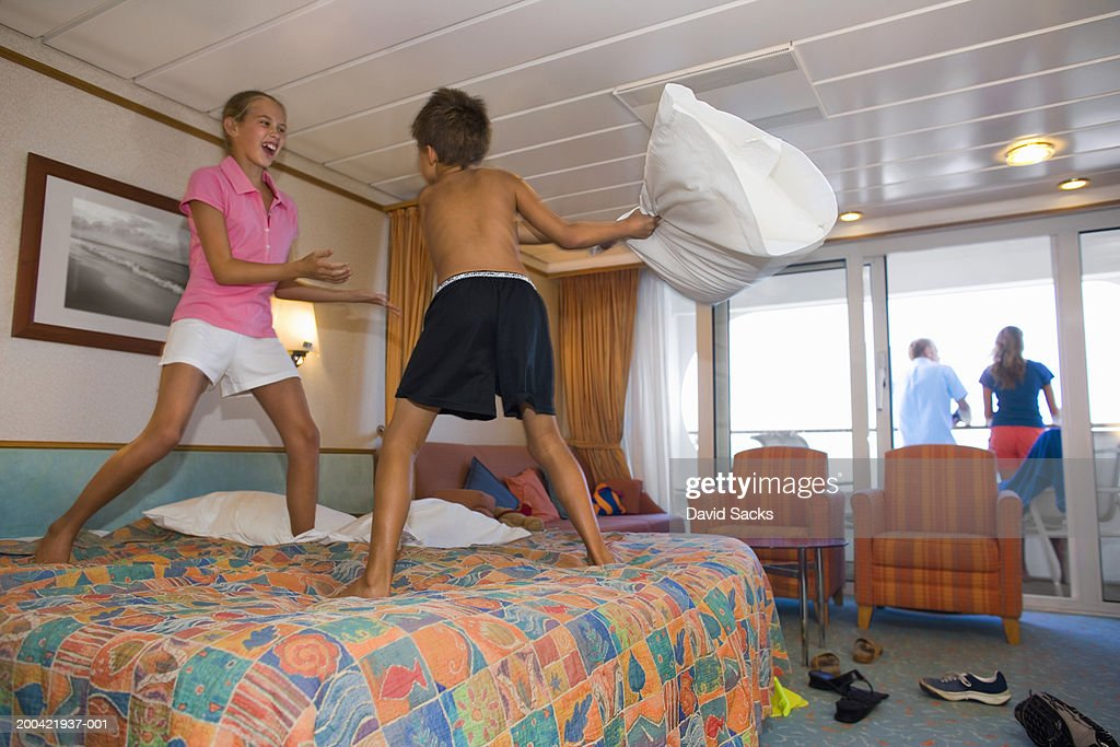 Brother and sister (10-12) having pillow fight on bed : Stock Photo