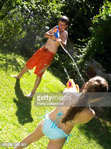 Brother And Sister 9 12 Having Water Fight In Garden Stock Photo