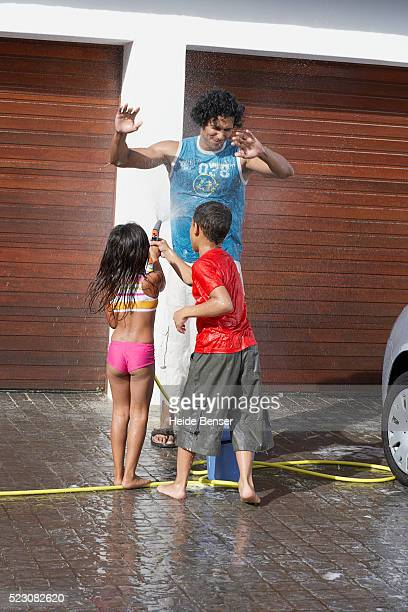 Brother and sister having water fight with father