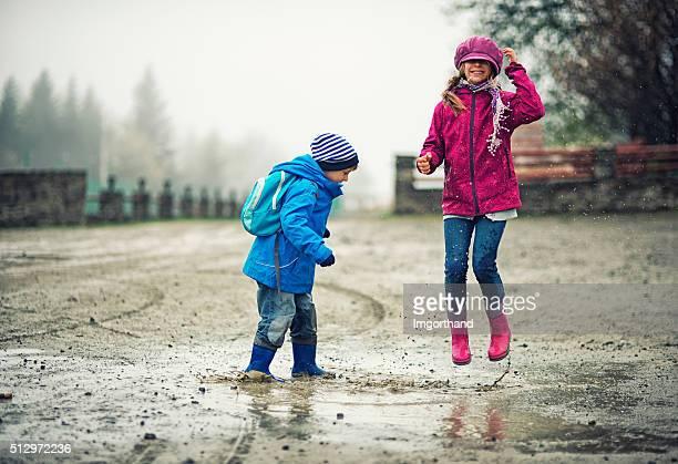 Bruder und Schwester spielt in einer Pfütze Wanderer