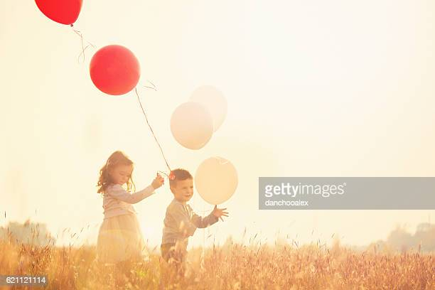 Brother and sister holding balloons and running
