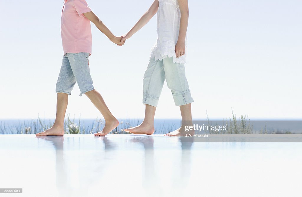Brother and sister holding hands near infinity pool