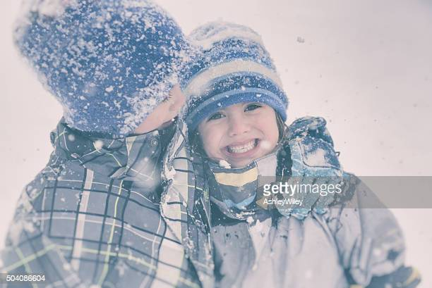 Brother and sister hug in a snowy storm