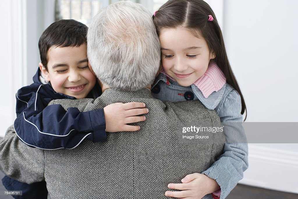 Brother and sister hugging grandfather