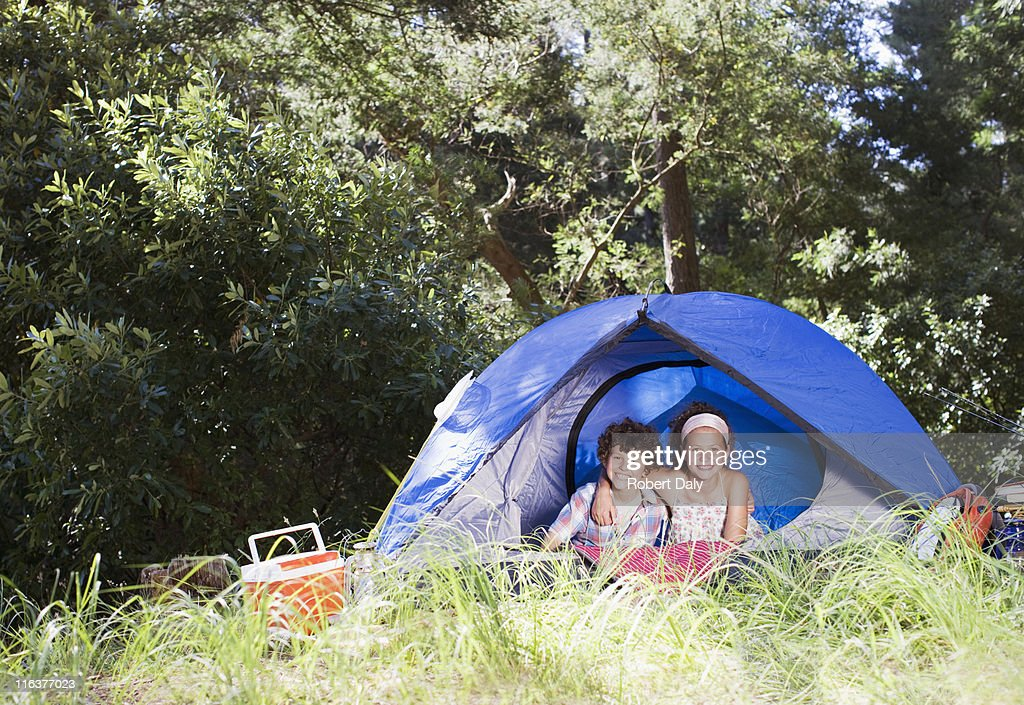Brother and sister hugging in tent : Stock Photo