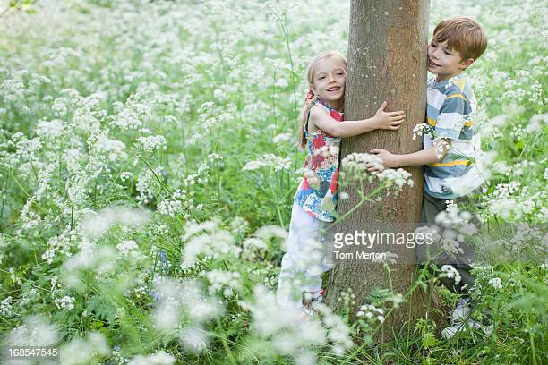 Brother and sister hugging tree