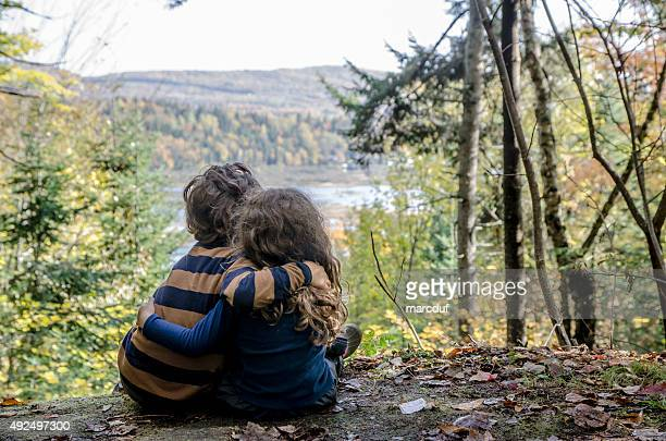 Brother and sister hugging while looking at nature