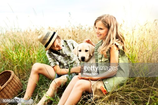 brother and sister in a wheat field with a dog : Stock Photo