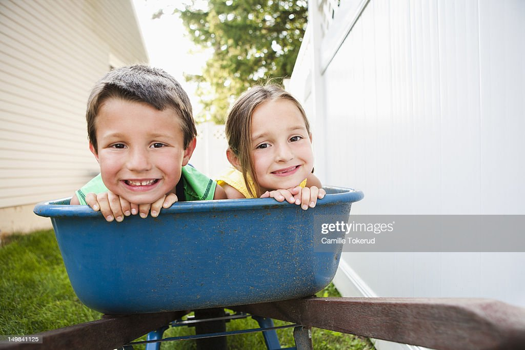 Brother and sister in a wheel barrel smiling : Stock Photo