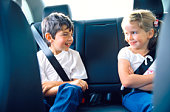 Brother and sister in backseat of car