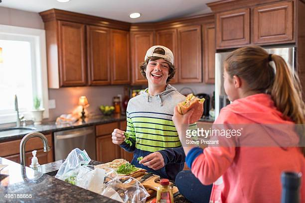 Brother and sister in kitchen preparing sandwich