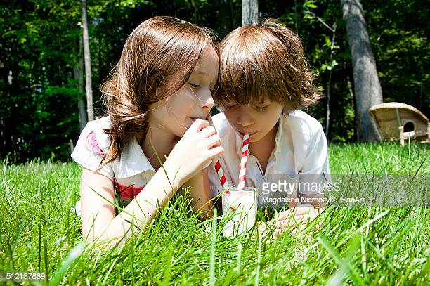 Brother and sister in woods sharing a milkshake