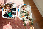 Brother and sister inside laundry baskets