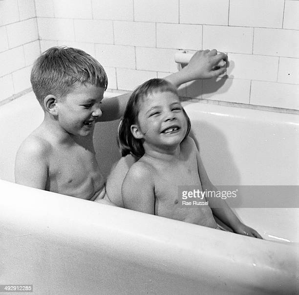 A brother and sister laugh as they sit together in a bathtub New York 1949