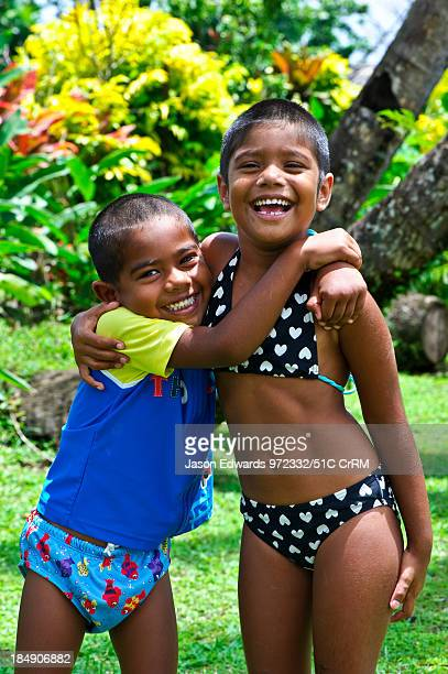 A brother and sister laughing and playing in a tropical garden Paradise Taveuni Taveuni Island Pacific Ocean Fiji Islands