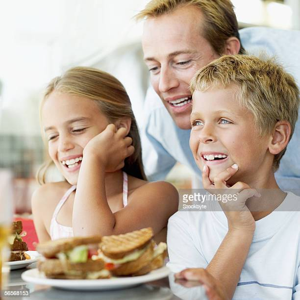 brother and sister laughing at the dining table with their father standing behind them