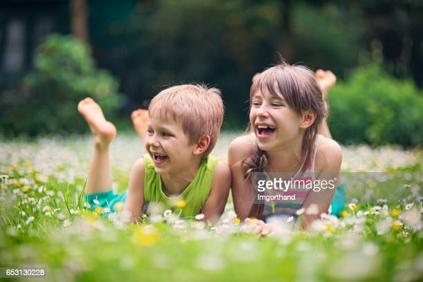 Brother and sister laughing in spring grass
