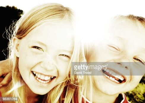 Brother and sister laughing in the sunlight : Stock Photo