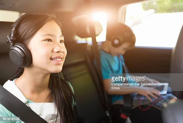 Brother and sister listening to headphones in car