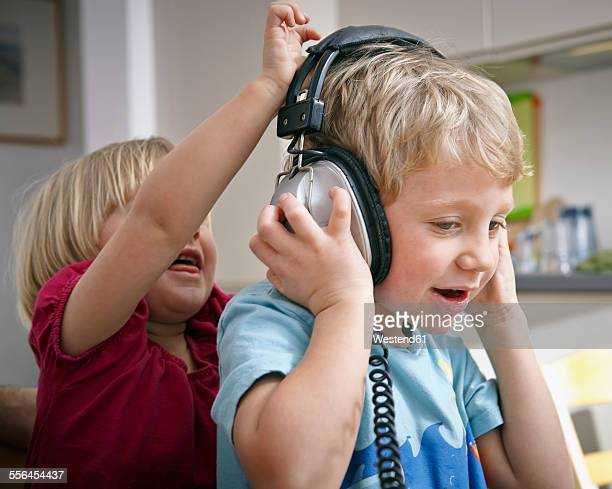 Brother and sister listening to music with headphones