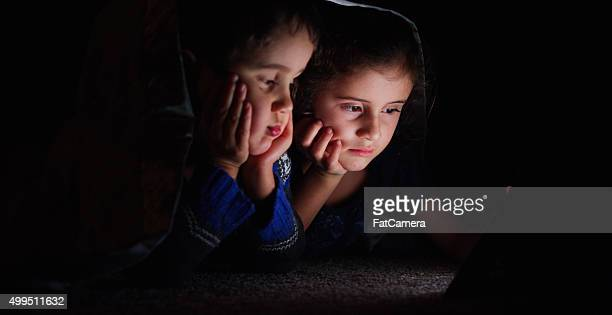 Brother and Sister Looking at a Tablet