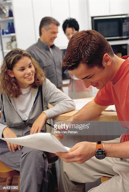 Brother and sister looking at paperwork while parents stand in background