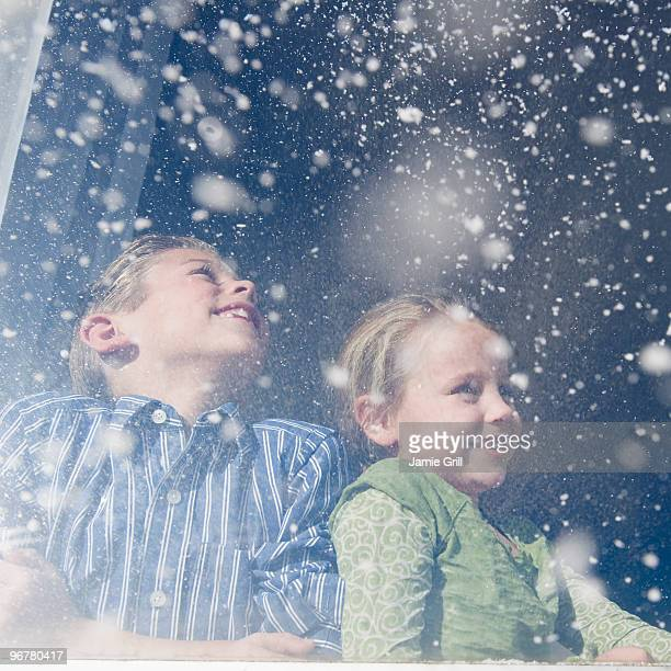 Brother and sister looking out window at snow