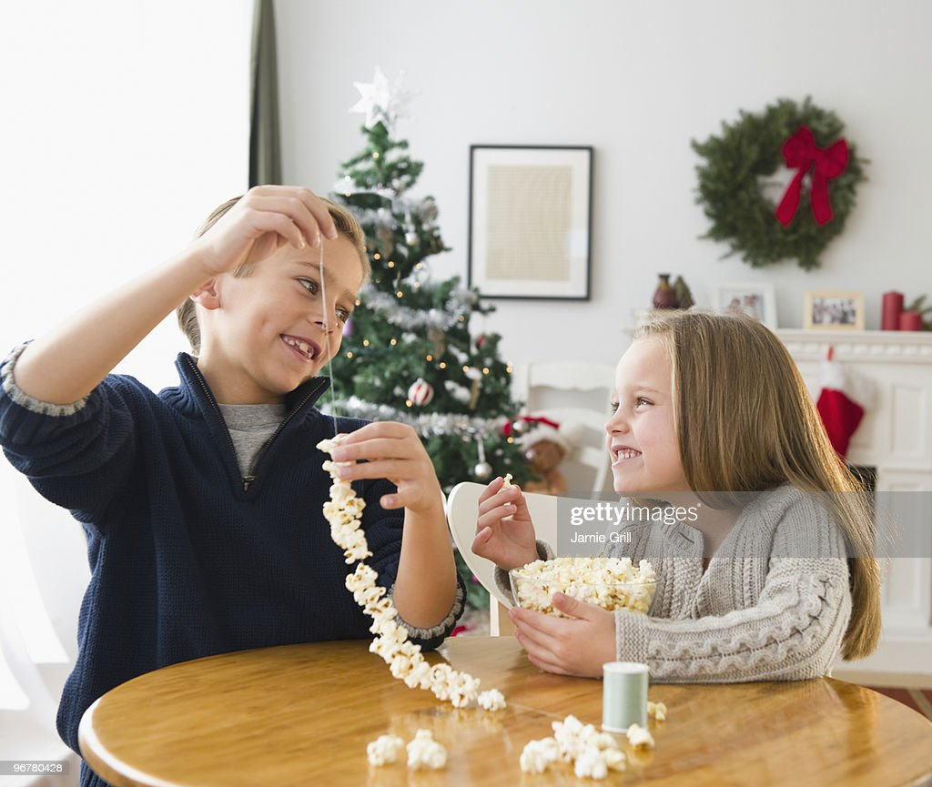 Brother and sister making popcorn garland : Stock Photo