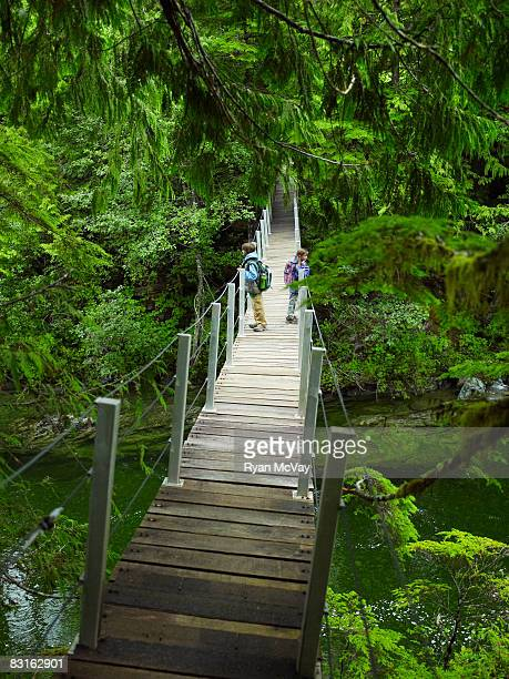 Brother and sister on suspension bridge over water