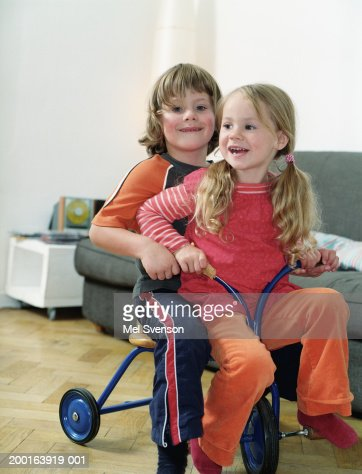 Brother and sister (4-6) on tricycle in living room, portrait of boy : Stock Photo