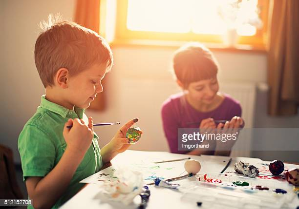 Brother and sister painting easter eggs