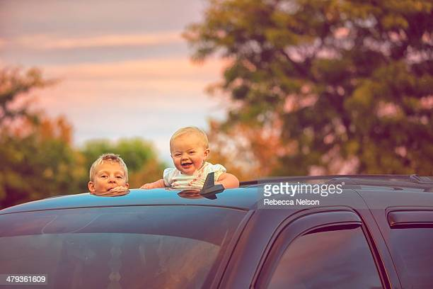Brother and sister peeking out of car sunroof