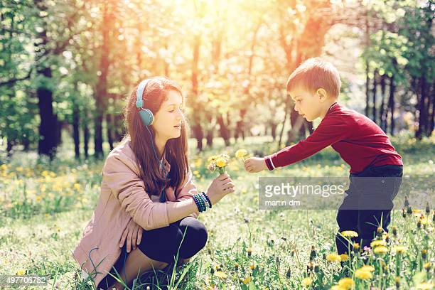 Brother and sister picking flowers in the park
