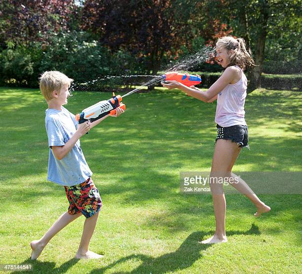 Brother and sister play fighting with water guns in garden