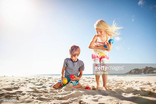 Brother and Sister playing boules on beach