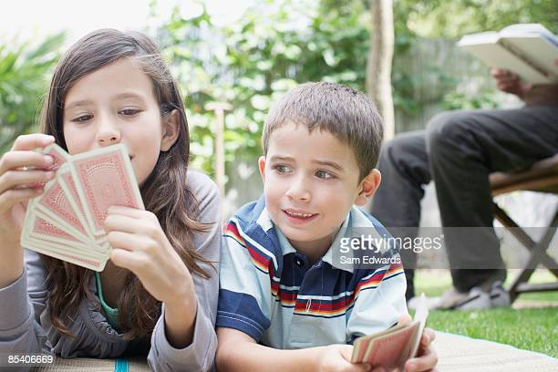 Brother and sister playing cards outdoors