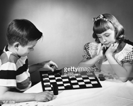 Brother and sister playing checkers at table