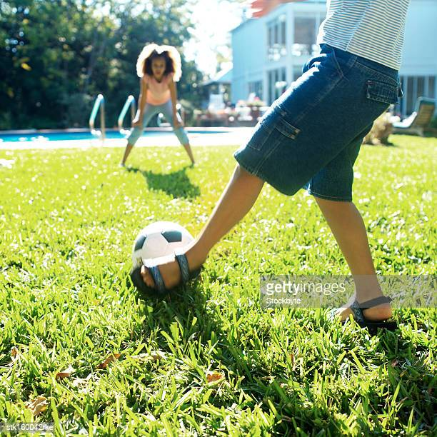 brother and sister playing football near a swimming pool