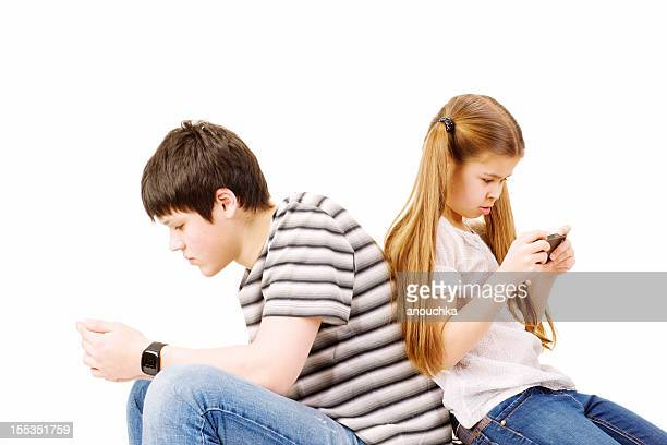 Frère et sœur jouant sur les téléphones mobiles