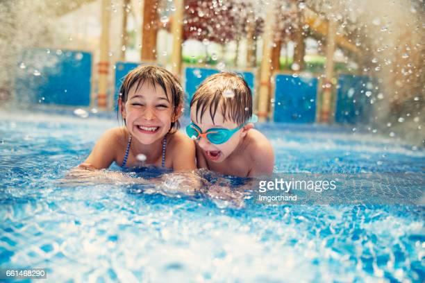 Bruder und Schwester im Resort Pool spielen.