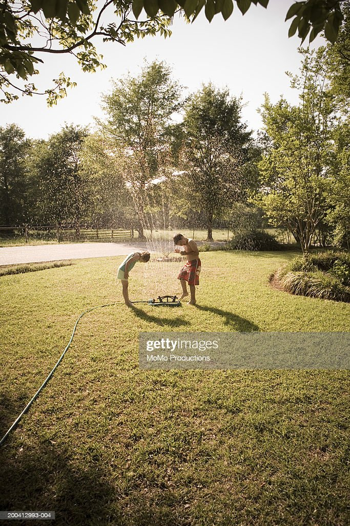 Brother and sister (6-8) playing in sprinkler : Stock Photo