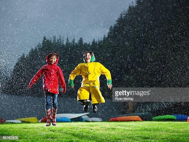 Bruder und Schwester Spielen im Regen.