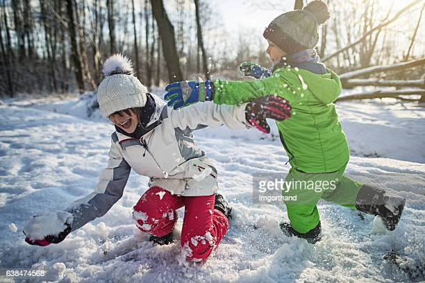 Brother and sister playing showball fight in winter forest