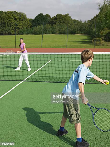 Brother and sister playing tennis