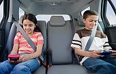 Brother and sister playing video games in car