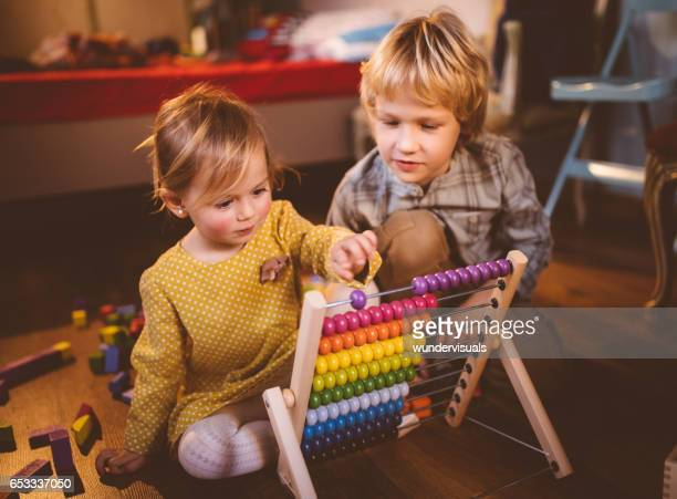 Brother and sister playing with abacus in their bedroom