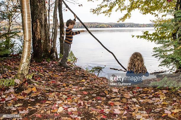 Bruder und Schwester spielen mit Ast am Ufer des lake