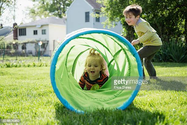 Brother (6-7) and sister (12-23 months) playing with toy tunnel in backyard