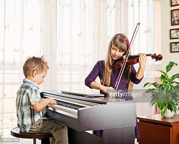Brother and sister practicing piano, violin