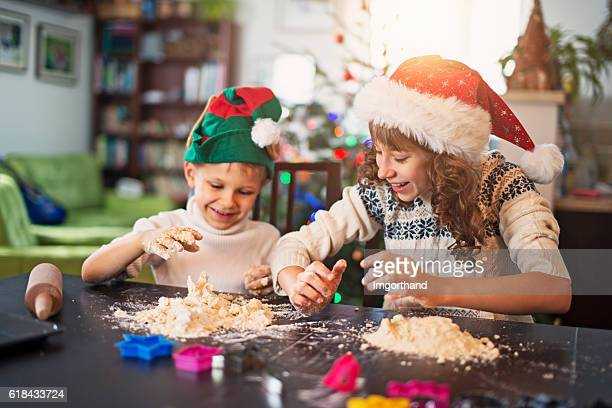 Brother and sister preparing christmas cookies